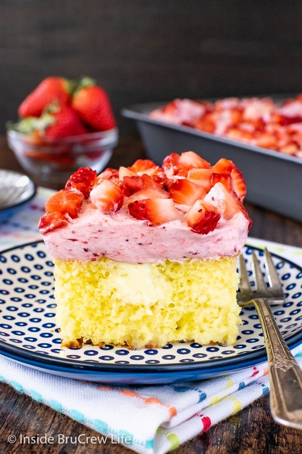 A square of lemon poke cake topped with strawberry mousse and fresh strawberries on a blue and white plate.