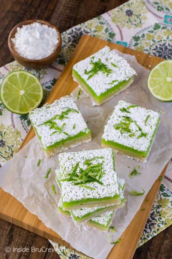 Key Lime Bars - a bright green key lime filling adds the perfect tart flavor to the sweet cookie crust. Great summer recipe for picnics and parties!
