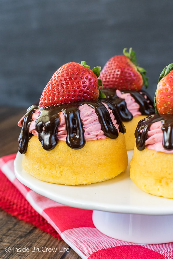 A white cake plate with three strawberry mousse cakes topped with chocolate drizzles and fresh strawberries.