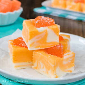 A stack of orange fudge on a white plate with more fudge behind it