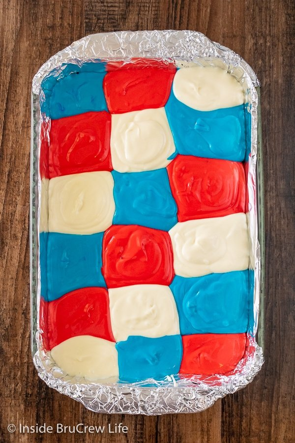 A pan of cheesecake bars with a grid of red white and blue colors