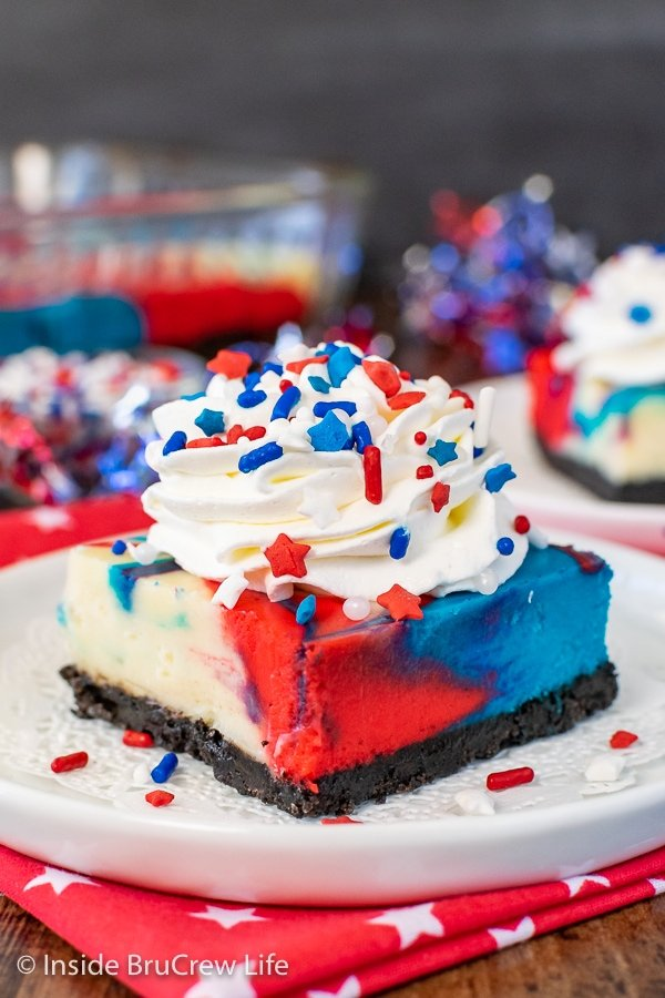 A white plate with a square of red white and blue swirled cheesecake topped with Cool Whip and sprinkles on it