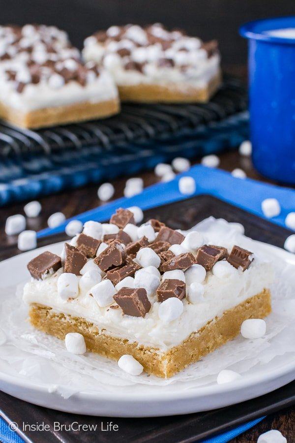 S'mores Sugar Cookie Bars - marshmallow frosting and chocolate chunks add a fun flair to these easy graham cracker cookie bars. Great recipe for summer picnics!