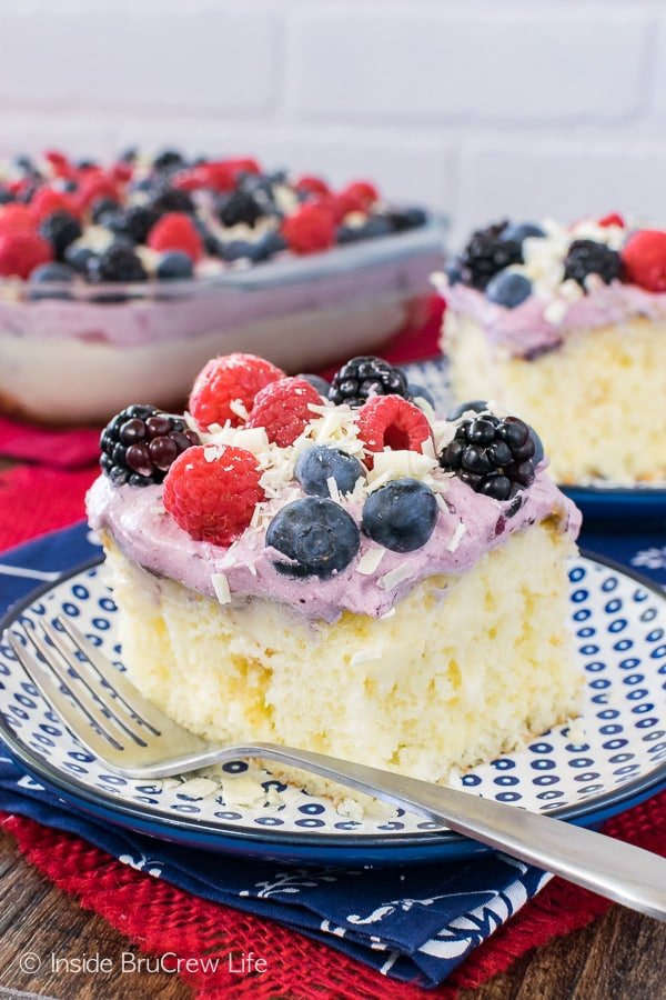 White Chocolate Berry Pudding Cake - sweet pockets of pudding and fresh berries make this poke cake so good. Perfect dessert recipe for summer parties and picnics!