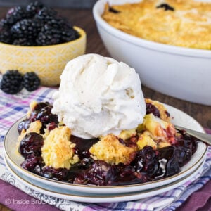 A white plate with scoop of blackberry dump cake topped with vanilla ice cream on it