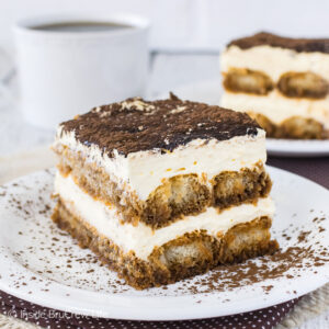 A white plate with a slice of easy tiramisu with cocoa powder on top in it