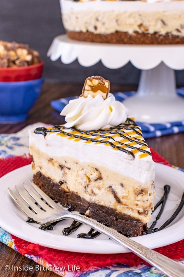 A white plate with hot fudge drizzles and a slice of snickers cheesecake with a brownie crust on it