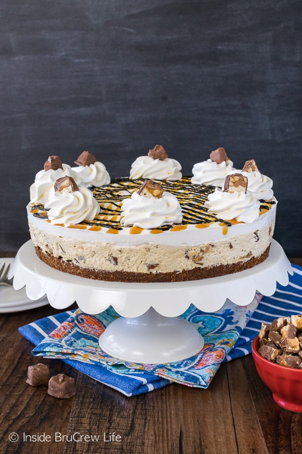 Snickers Cheesecake Brownie Cake - a layer of homemade brownie topped with candy loaded cheesecake. Easy dessert recipe for any party!