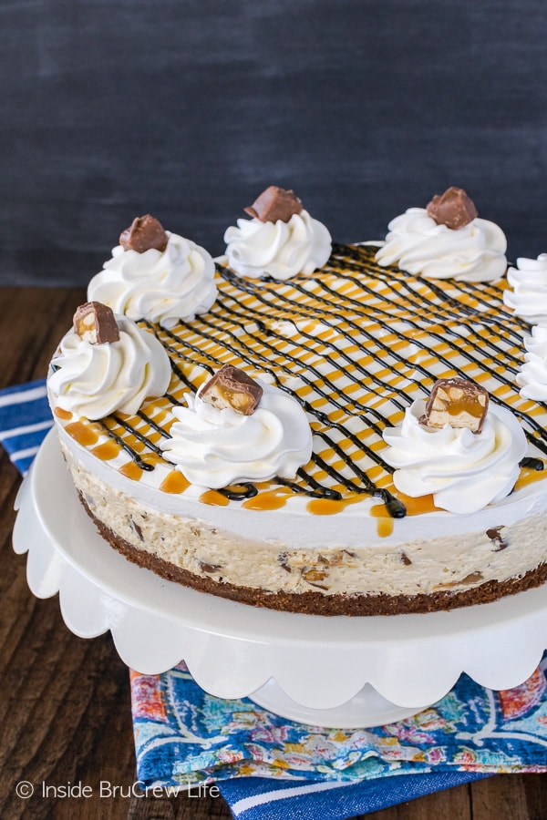 Snickers Cheesecake Brownie Cake - chocolate and caramel drizzles add a fun flair to this easy layered dessert. Great recipe for any party!