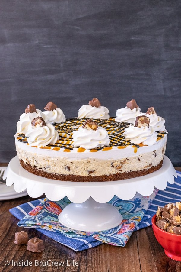 A white cake plate on a blue towel with a full sized Snickers Cheesecake with a brownie crust sitting on it
