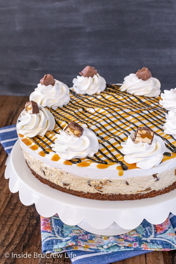 A white cake plate on a blue towel with a No Bake Snickers Cheesecake with a brownie crust on it