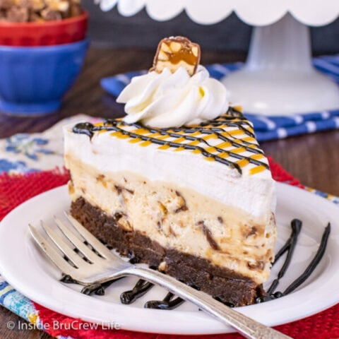 A white plate with a slice of snickers cheesecake with a brownie bottom on it