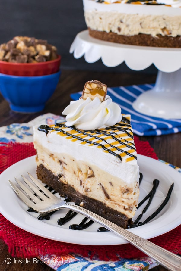 Snickers Cheesecake Brownie Cake - creamy cheesecake loaded with candy bars layered with homemade brownies. Great dessert recipe for any party!