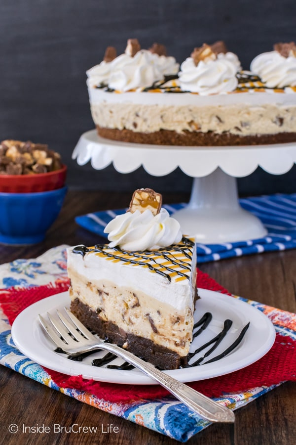 Snickers Cheesecake Brownie Cake - three layers make this easy cake a fun treat for any party. Homemade brownies with candy loaded cheesecake will get rave reviews!