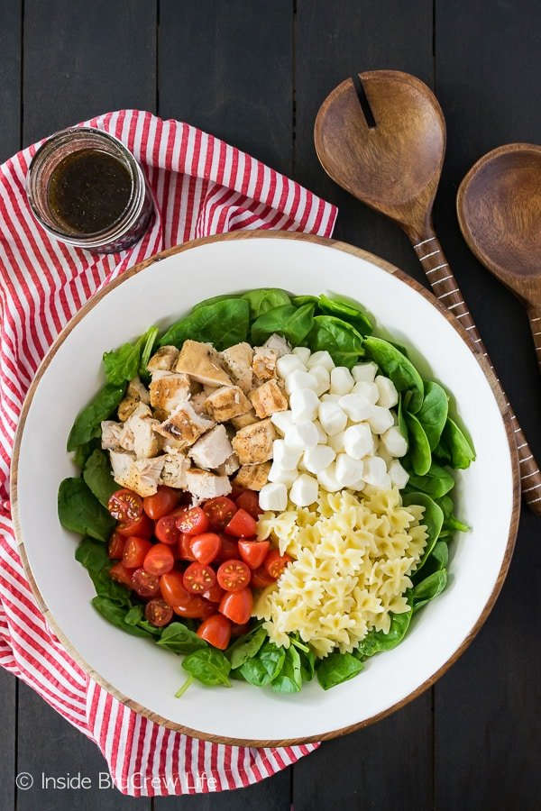 Spinach Chicken Caprese Salad - a big bowl of veggies, meat, and cheese drizzled in homemade dressing make a perfect light meal! Easy recipe to put together on busy days!