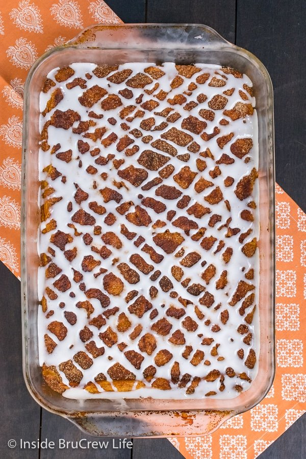 Overhead picture of a pan of churro pumpkin pie cheesecake danish drizzled with a sweet glaze