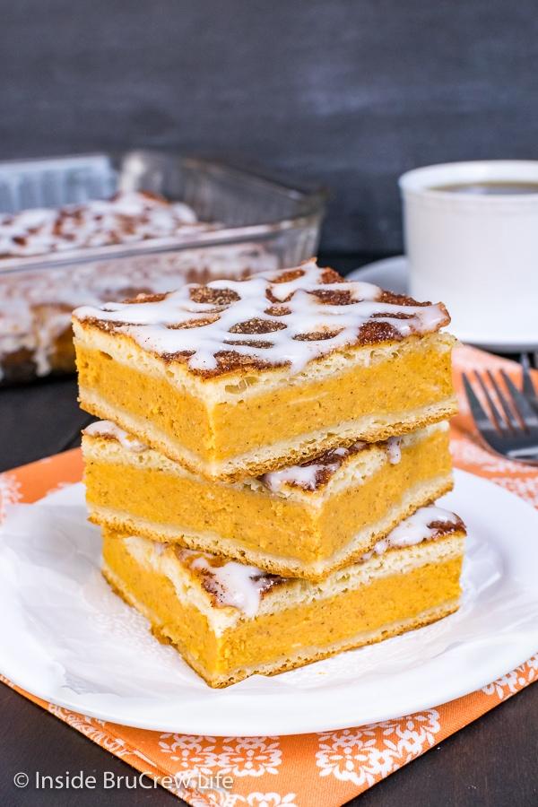 Three squares of churro pumpkin pie cheesecake danish on a white plate