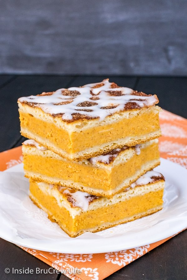 A stack of three churro pumpkin pie cheesecake danishes on a white plate
