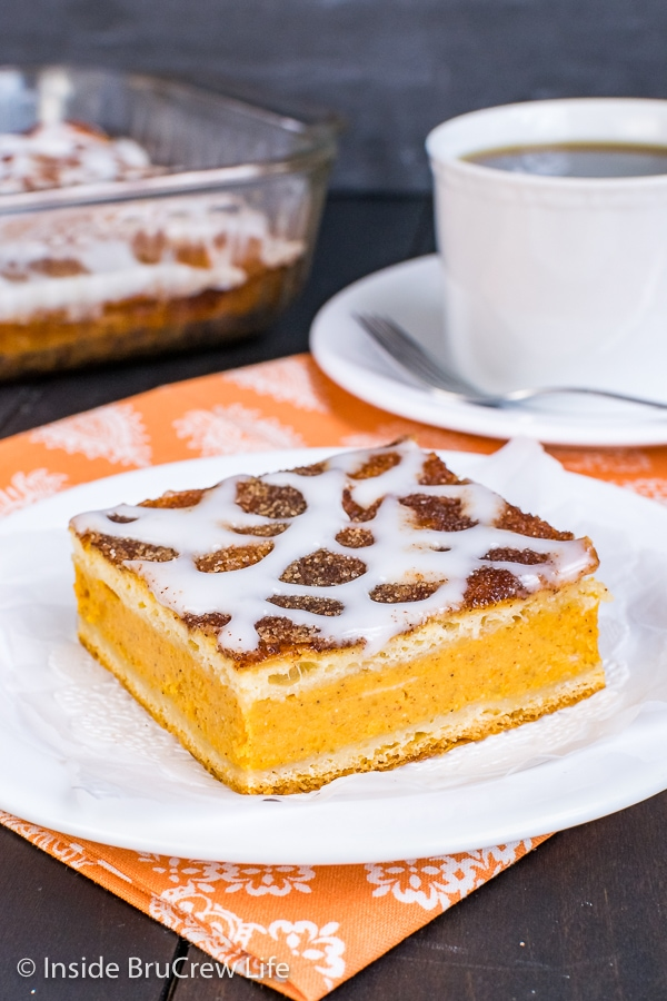 A white plate with a square of churro pumpkin pie cheesecake danish drizzled with a sweet glaze on it