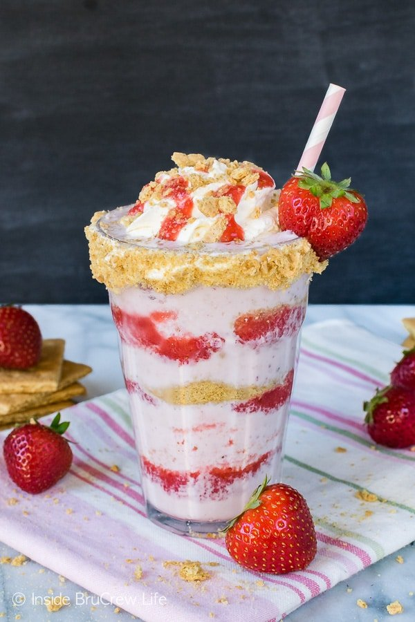 Strawberry Cheesecake Milkshakes - layers of cookie crumbs, strawberry sauce, and a sweet strawberry milkshake makes a fun frozen drink. Easy recipe for a hot summer day!