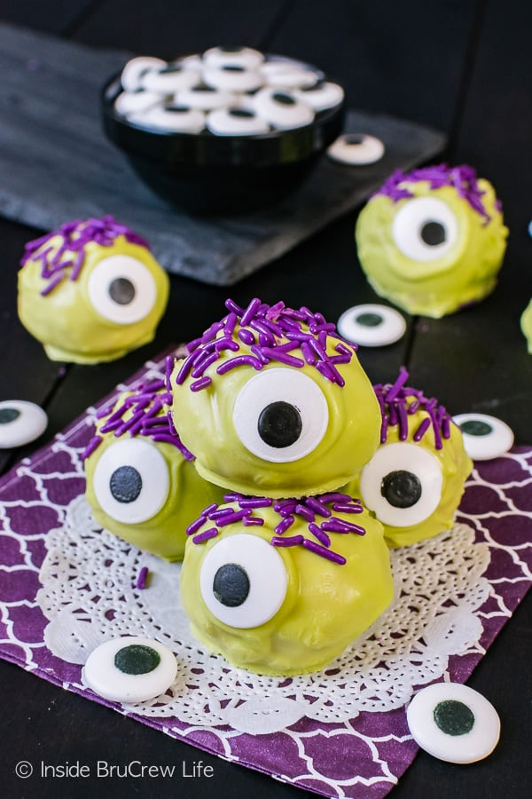 Peanut Butter Monsters - green chocolate, candy eyes, and purple sprinkles turn these easy candies into a fun treat. Easy no bake recipe for halloween parties!