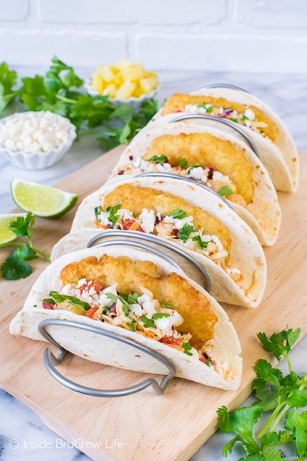 A metal taco holder with four easy fish tacos in it filled with crispy fish, slaw, and cheese