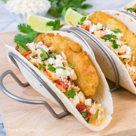A flour tortilla in a taco stand filled with crispy fish, slaw, and cheese