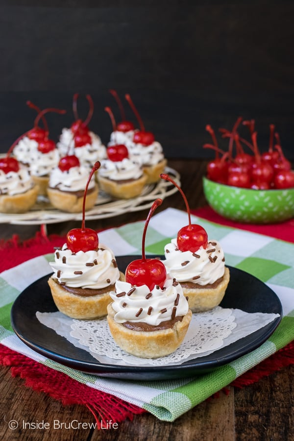 Chocolate Cheesecake Pie Bites - little mini pies filled with chocolate cheesecake. Cherries with stems and sprinkles make them look fancy. Easy recipe to make for dessert! #dessert #cheesecake #pie #chocolate #minidesserts #easy #recipe #smalldesserts
