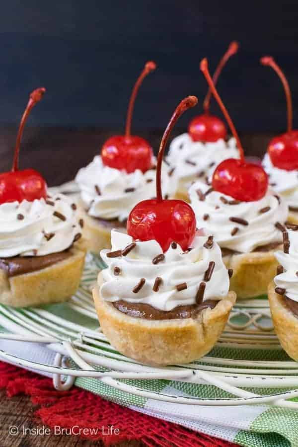 Chocolate Cheesecake Pie Bites - mini pies filled with chocolate cheesecake and topped with whipped cream and cherries. Easy recipe to make for dessert! #dessert #cheesecake #pie #chocolate #minidesserts #easy #recipe #smalldesserts