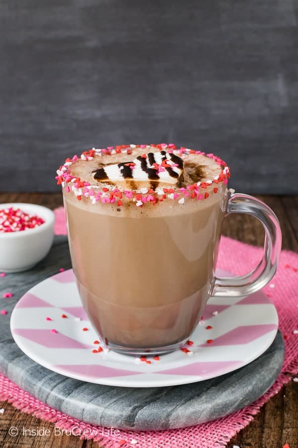 A glass cup of Dark Chocolate Latte with a rim of pink and red heart sprinkles sitting on a pink and white plate