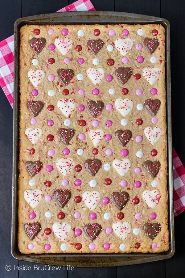 Valentine Peanut Butter Heart Cookie Bars - easy cookies made in a sheet pan and loaded with candies! Great recipe for Valentine's day parties! #cookies #peanutbutter #peanutbutterhearts #valentine #valentinesdaytreats #cookiebars #dessert #reeses