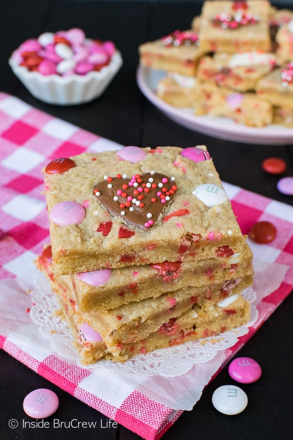 Valentine Peanut Butter Heart Cookie Bars - easy cookie bars loaded with peanut butter hearts, candies, and sprinkles. Easy recipe to make for Valentine's day parties! #cookies #peanutbutter #peanutbutterhearts #valentine #valentinesdaytreats #cookiebars #dessert #reeses