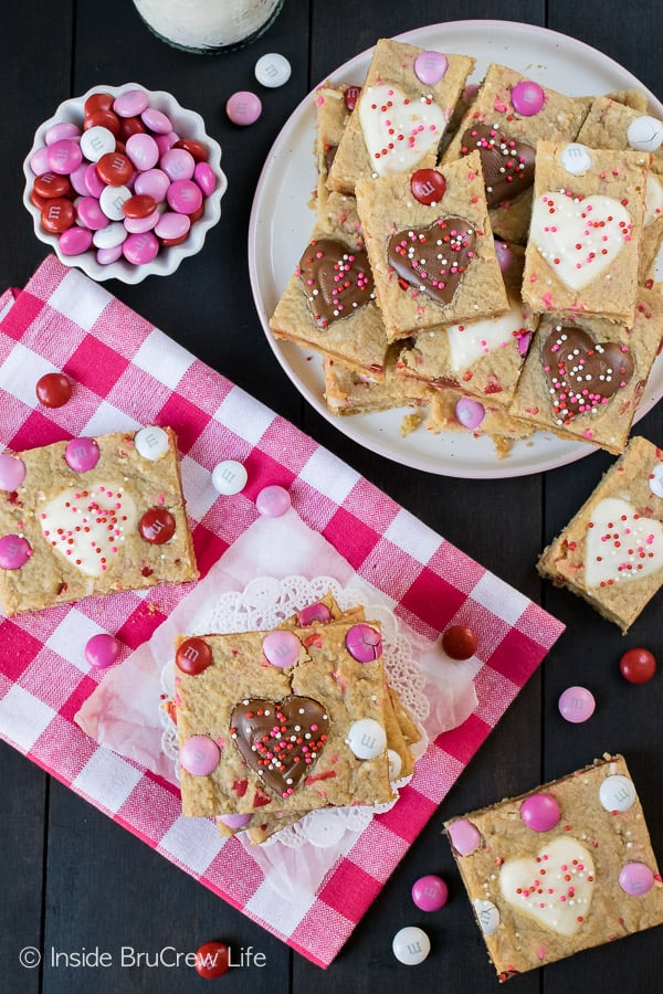 Valentine Peanut Butter Heart Cookie Bars - soft peanut butter bars topped with peanut butter hearts, sprinkles, and candies. Great recipe for Valentine's day parties! #cookies #peanutbutter #peanutbutterhearts #valentine #valentinesdaytreats #cookiebars #dessert #reeses