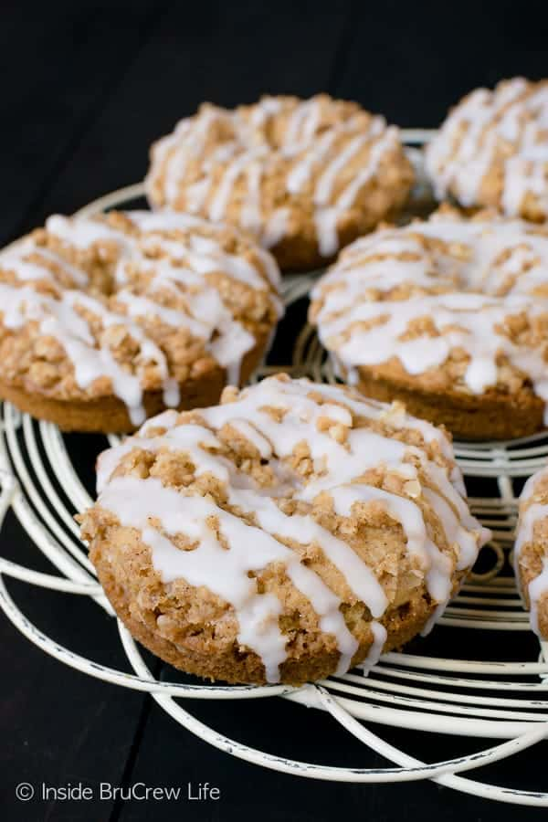 Cinnamon Crumble Donuts - a warm cinnamon spice baked donut topped with crunchy cinnamon crumble and glaze is a delicious way to start any day. Great homemade donut recipe for breakfast, brunch, or afternoon coffee. #donuts #cinnamon #homemade #coffeetime #brunch #breakfast #cakedonuts #baked