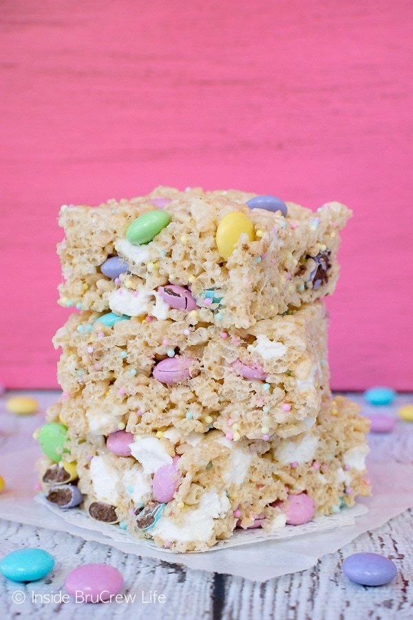 Three Easter rice krispies treats with M&M candies and sprinkles stacked on top of each other on a pink board