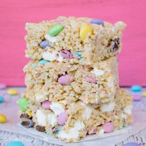 A stack of three Easter rice krispies treats stacked on top of each other with a pink background