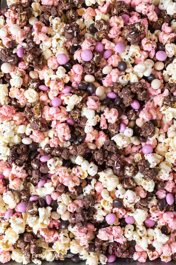 Neapolitan Popcorn - three kinds of chocolate and candies make this easy snack mix a fun treat to make and eat. Great no bake recipe for movie night. #popcorn #chocolate #strawberry #nobake #snackmix #neapolitan