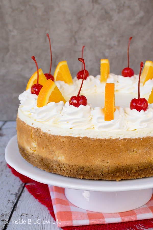 Orange Cream Cheesecake - cherries and orange slices add a pretty flair to the top of this orange loaded cheesecake. This creamy dessert recipe is perfect for spring or summer parties or picnics. #cheesecake #orange #macadamianuts #dessert #recipe #orange #spring #summer