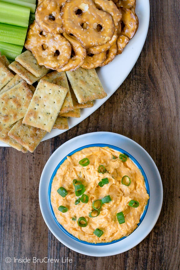 Overhead picture of a blue bowl filled with buffalo chicken dip and a white plate with crackers, pretzels, and celery on it