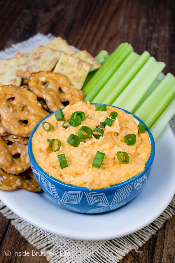 A white plate with crackers, celery, pretzels, and a blue bowl filled with buffalo chicken dip on it