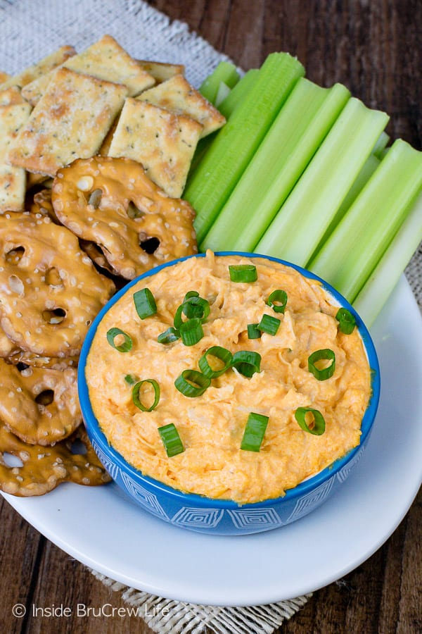 Overhead picture of a white plate with a blue bowl filled with buffalo chicken dip and pretzels, crackers, and celery