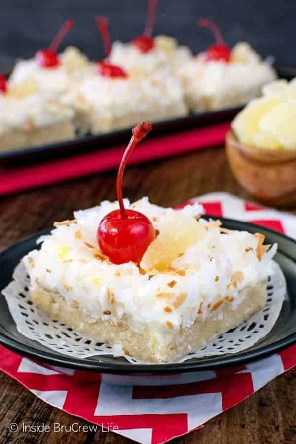 Pina Colada Sugar Cookie Bars - these easy cookie bars are loaded with coconut and pineapple. The creamy frosting and chewy cookies are the perfect tropical treat. Make this easy recipe for dessert or summer picnics. #sugarcookiebars #easy #dessert #frosting #pinacolada #pineapple #coconut #barcookies #bakesale