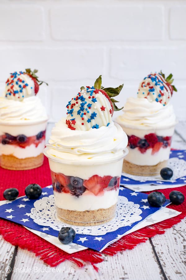 No Bake White Chocolate Cheesecake Parfaits - easy layers of cookies, cheesecake mousse, and fresh fruit makes a fun holiday dessert. Make this easy cheesecake recipe for parties and picnics! #cheesecake #nobake #easydesserts #strawberry #blueberry #whitechocolate #nobakecheesecake