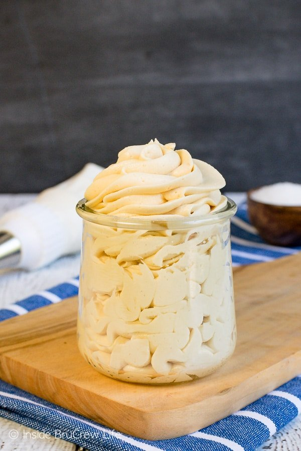 A clear jar filled with a swirl of salted caramel icing in it.