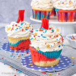 Two red white and blue cupcakes with candy fuse on top.