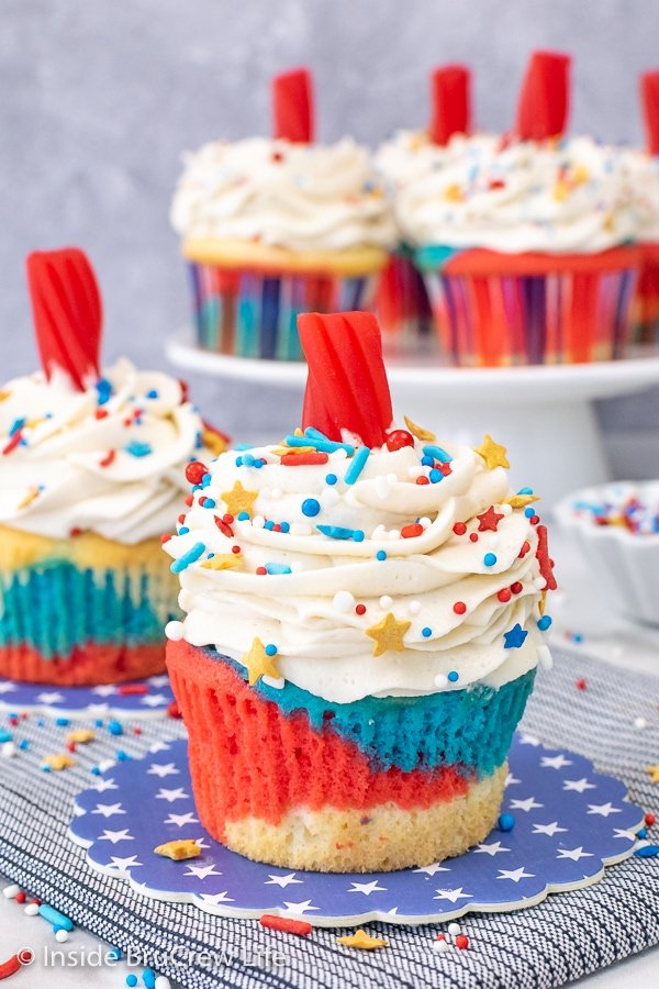 Two red white and blue firecracker cupcakes with vanilla frosting, sprinkles, and twizzlers on blue coasters.