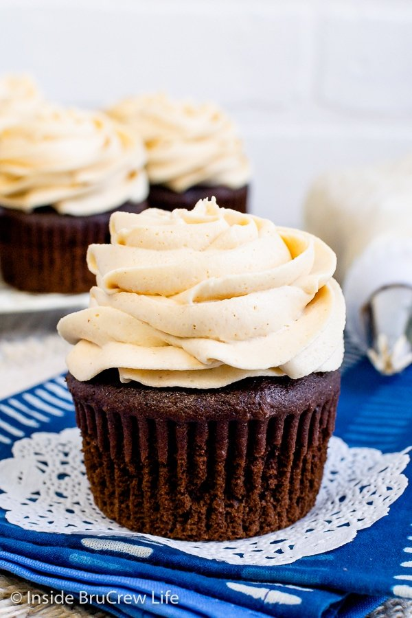 A chocolate cupcake with a swirl of peanut butter frosting on it and more cupcakes behind it.