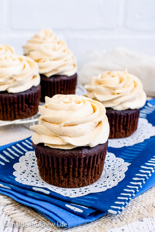 Two chocolate cupcakes with peanut butter frosting swirls on a blue towel.