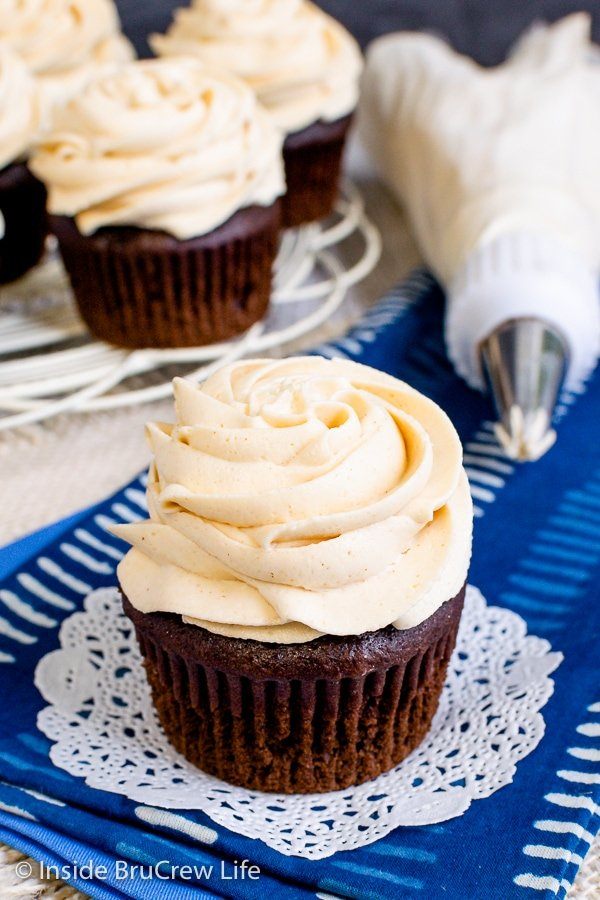 A chocolate cupcake on a blue towel with a swirl of peanut butter icing on top.