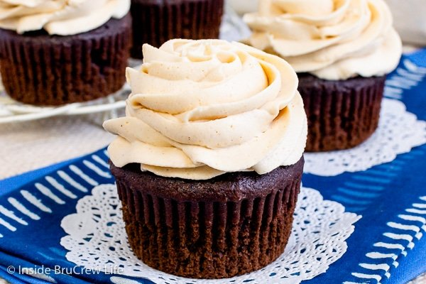Two chocolate cupcakes on a blue towel with a swirl of peanut butter icing on them.
